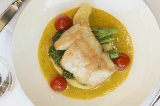 Wild Gulf Barramundi fillet oven baked, served on coconut curried sauce, potatoes, greens and tomatoes