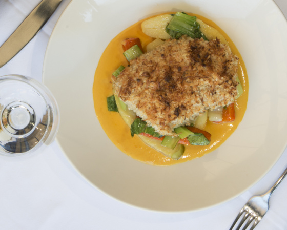 Wild Gulf Barramundi fillet baked with macadamia and coconut crust, served with vegetables, potato and a mango coconut sauce.